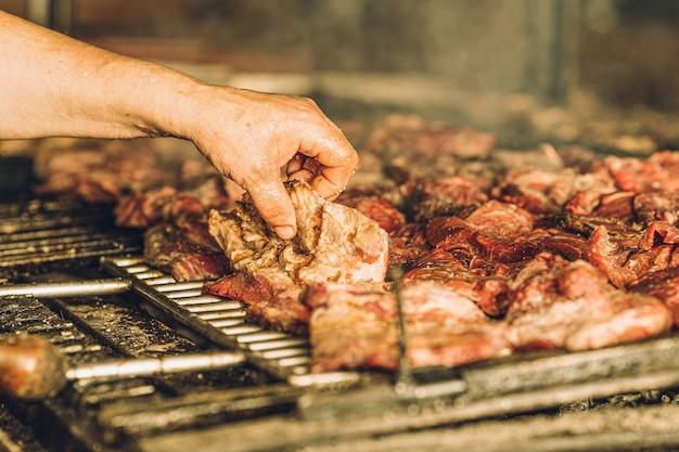 Неизвестный повар готовит куски мяса на гриле и руками.
