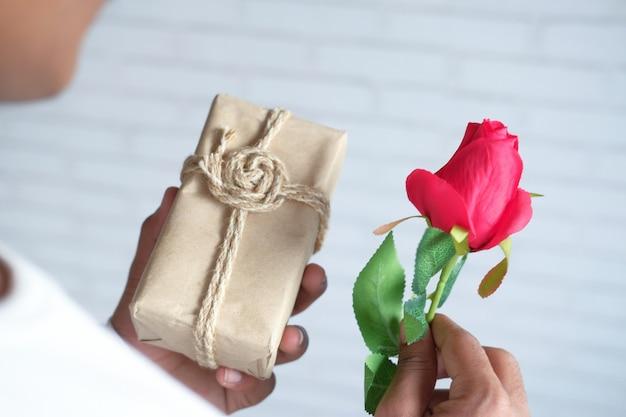 バラの花とギフトボックスを持っている認識されていない男の手がクローズアップ