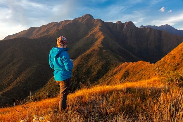 山岳風景でセルラースマートフォンを使用している認識されていない人々