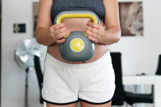 Неизвестная беременная женщина, тренирующаяся с гирей в гостиной.