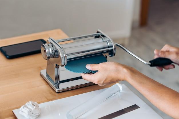 自宅でカラフルな手作りジュエリーを作成している認識されていない女性。