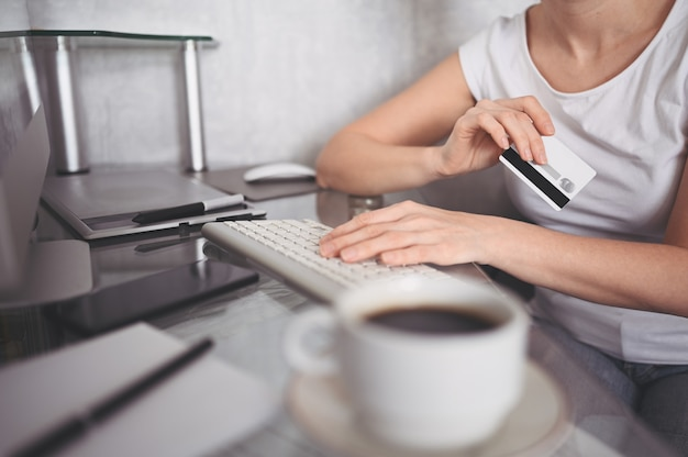 Unrecognized woman holding credit card in hand and using laptop computer keyboard. businesswoman or entrepreneur working. online shopping, e-commerce, internet banking, spending money concept