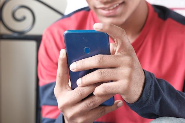 Неизвестный молодой человек сидит на кровати с помощью смартфона.