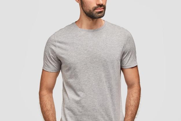 До неузнаваемости бородатый мужчина, одетый в повседневную серую футболку