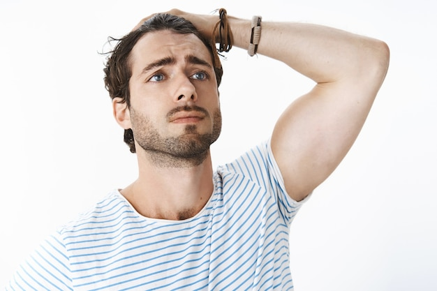 Unretouched shot of dramatic upset good-looking guy with beard and mascules combing hair behind with hand making sad look on distance as if acting in drama movie feeling conserned and sad