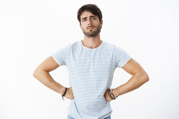 수염과 파란 눈을 가진 잘생긴 유럽 남자의 보정되지 않은 사진 친구가 약속을 어기고 찡그린 표정을 하고 허리에 손을 잡고 으르렁거리며 판단하면서 속상하고 실망했습니다.