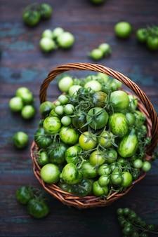 かごの中の有機トマトの未熟作物