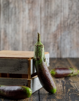 Unripe eggplants with wooden box side view on a wooden