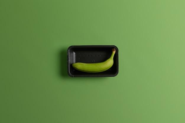 黒のトレイに未熟な緑のバナナ。あなたの消費のためのトロピカルフルーツ。上からの眺め。健康的なライフスタイルと栄養。果物と食品のコンセプト。果樹園から集められた単一のバナナ。鮮やかな背景
