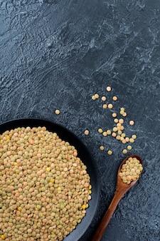 Unripe green raw lentils in a black ceramic dish on a black background.