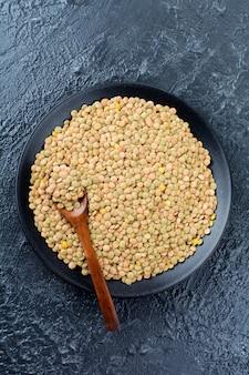 黒い表面の黒いセラミック皿に未熟な緑色の生レンズ豆