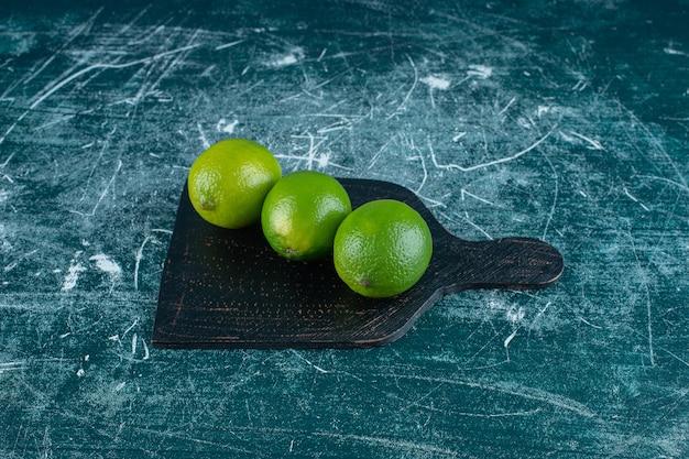 Незрелые лимоны на разделочной доске, на мраморном фоне. фото высокого качества