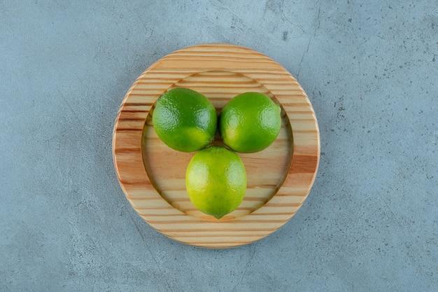Незрелые лимоны на деревянной тарелке, на мраморном фоне. фото высокого качества