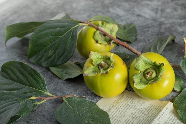 大理石の表面に葉と本のページを持つ未熟な柿