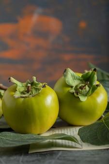 大理石の背景に葉を持つ未熟な柿