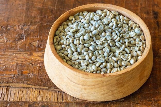 나무 그릇에 볶지 않은 녹색 커피 콩