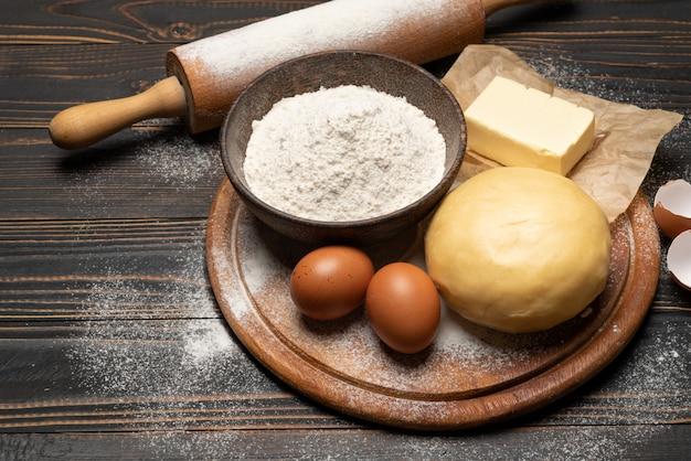 Раскрученный и невыпеченный рецепт песочного теста на деревянном фоне