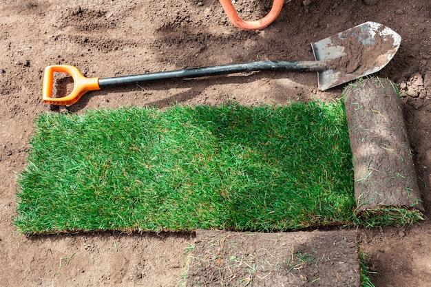 Раскатанный зеленый рулон газона на земле