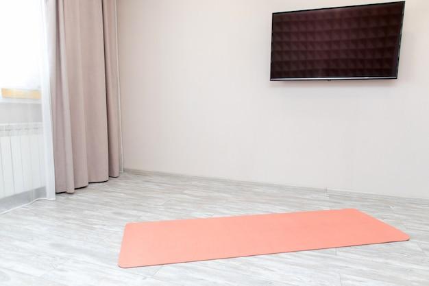 リビングルームの床に広げられたピンクのヨガマット