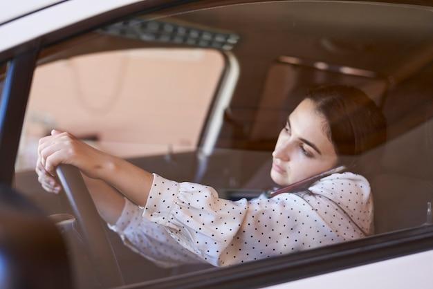 운전 중 전화 통화를 하는 안전하지 않은 운전 젊은 다인종 여성