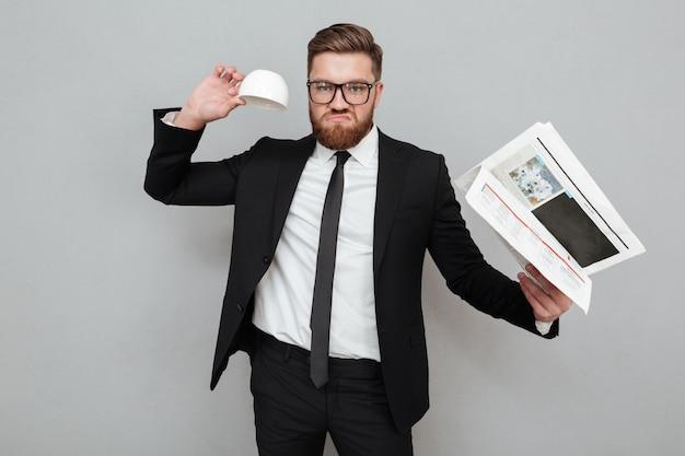 Неудовлетворенный бородатый бизнесмен в костюме и очках