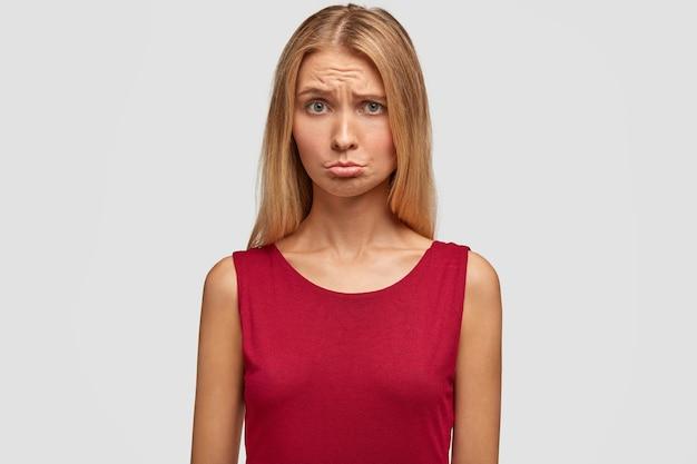 Недовольная красивая женщина поджимает губы, с обиженным выражением лица, чувствует себя несчастной после выяснения отношений с парнем, одетая в красную повседневную футболку, изолированную на белой стене