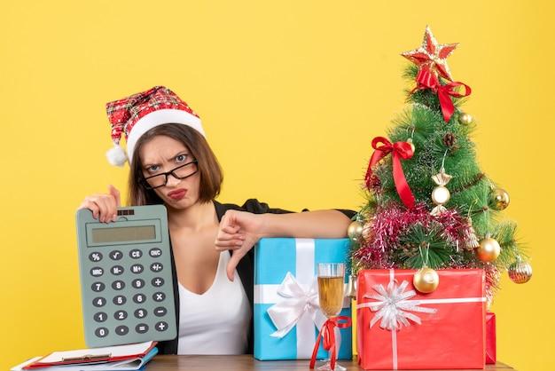黄色の孤立したオフィスで電卓が否定的なジェスチャーをしていることを示すサンタクロースの帽子とスーツを着た不満の魅力的な女性