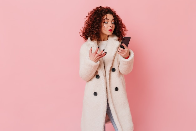Unsatisfied girl looks angry at phone screen. portrait of curly woman with bright lips dressed in white coat on pink space.