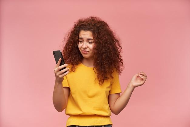 不満そうな女性、黄色いtシャツを着た生姜の巻き毛の女の子