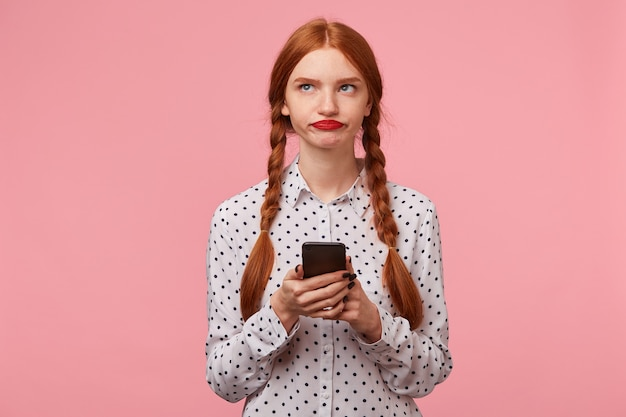 Unsatisfied red-haired girl with two braids without enthusiasm looking in the upper left corner trying to think of what to write in a message to her friend holding the phone in her hands, on pink wall