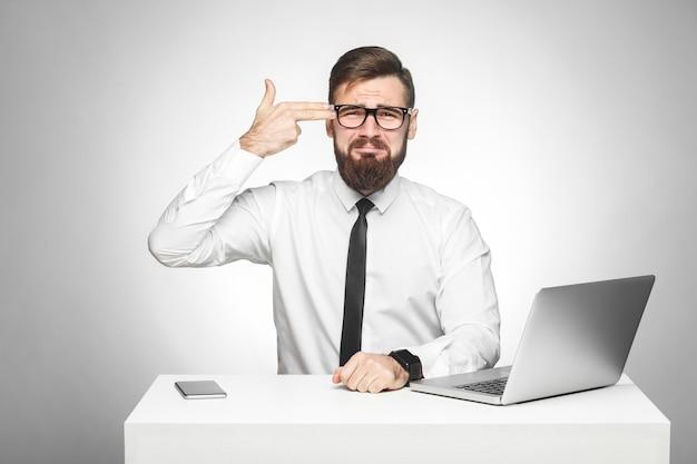 白いシャツと黒いネクタイを着た満足できないストレスのたまった疲れた若いマネージャーがオフィスに座って、指ピストルでサインを見せて自殺しようとしています。スタジオショット、孤立した、灰色の背景、屋内