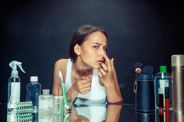 黒のスタジオの背景に鏡で自分自身を見ている不満の不幸な若い女性。問題のある肌とニキビの概念。スタジオでの白人モデル