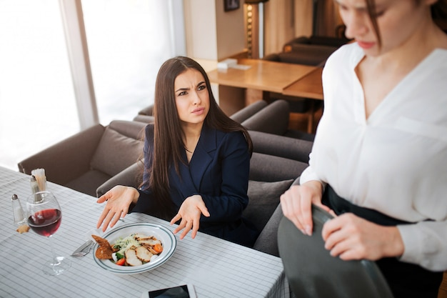 Unsatisfied young businesswoman complain about salad on table. she point on it and look at waitress.  young woman in white blouse is upset.