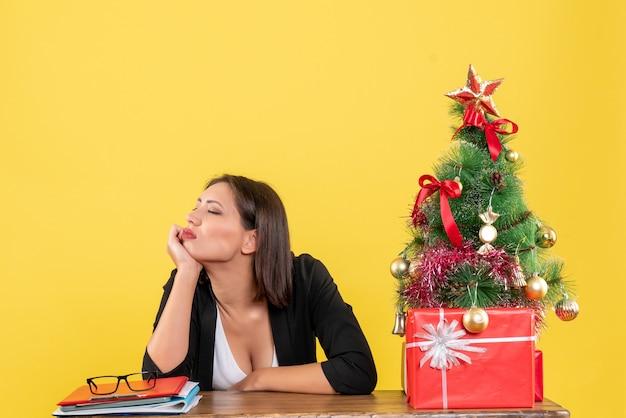 Giovane donna insoddisfatta in vestito vicino all'albero di natale decorato in ufficio su giallo