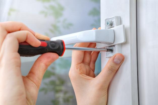 Unscrewing screw handles plastic window with hand tool.