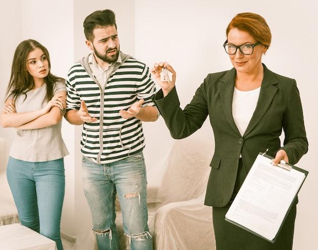 Недобросовестные съемщики спорят с агентом по недвижимости, который держит в руках ключи и документы.