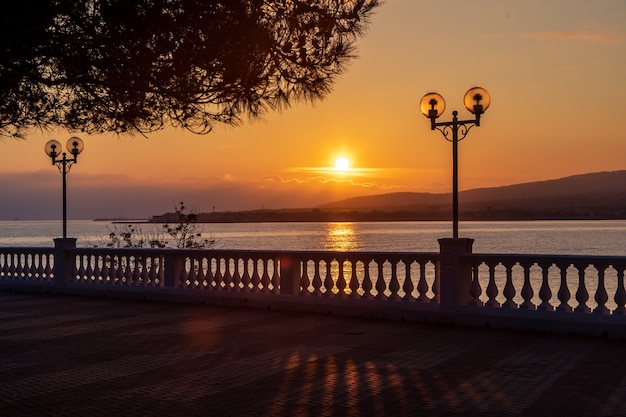 Unset on the resort embankment with balustrade and lanterns. the sun sets in the mountains and is reflected in the sea. pine branch in the foreground.the resort of gelendzhik.