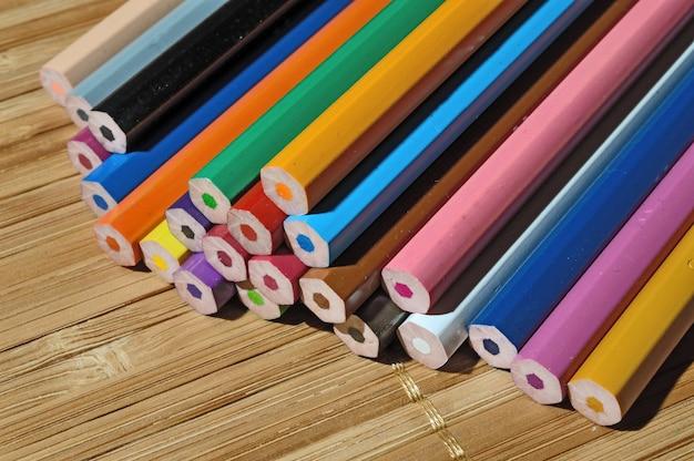 木製のテーブルの上に積み重ねられたシャープでない色鉛筆。