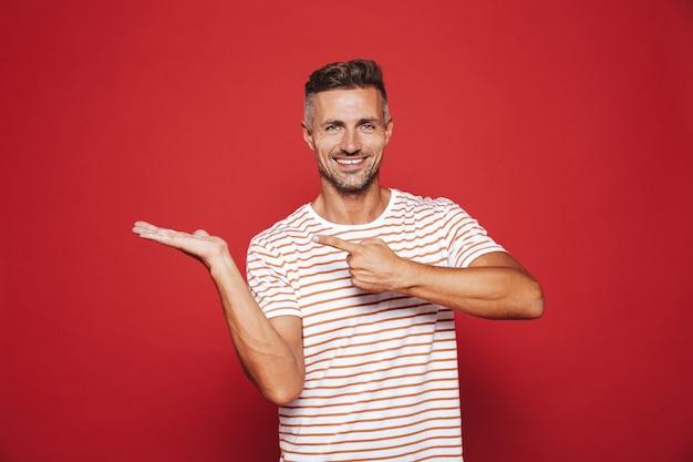 Небритый парень в полосатой футболке показывает указательными пальцами на ладони, изолированной на красном