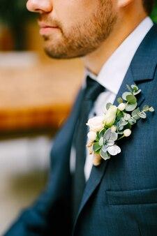 青いジャケットの白いシャツのネクタイと小さなバラとエケベリアのブートニアを持つ剃っていない男