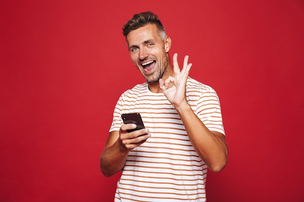 赤で隔離のスマートフォンを笑顔で保持している縞模様のtシャツの剃っていない男