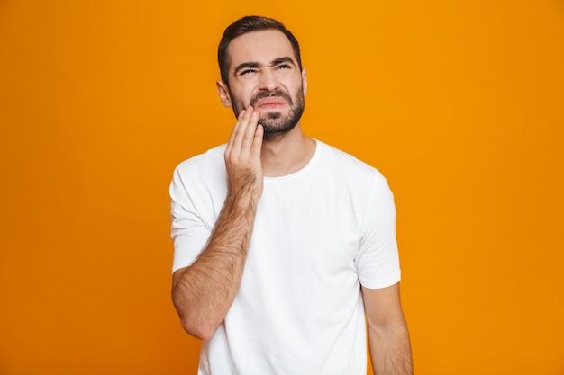 노란색에 고립 된 동안 그의 뺨을 만지고 치통으로 고통받는 티셔츠에 면도하지 않은 남자