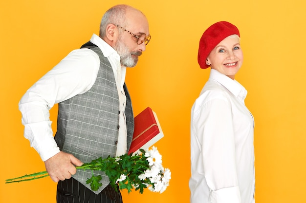 Unshaven bald elderly man wearing elegant clothes holding bunch of daisies and bof of chocolate, making birthday present to his charming wife. people, age, marriage and relationships concept