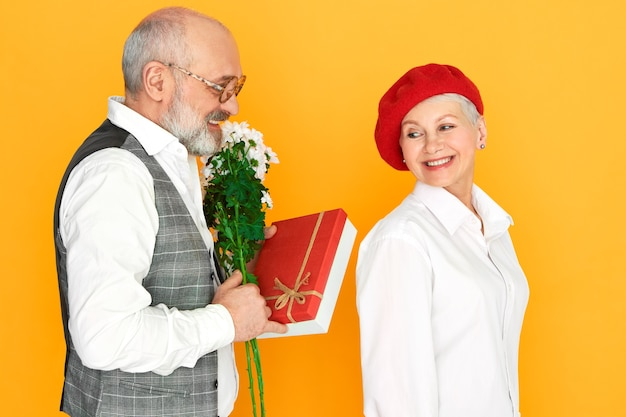 Unshaven bald elderly man wearing elegant clothes holding bunch of daisies and bof of chocolate, making birthday present to his charming wife