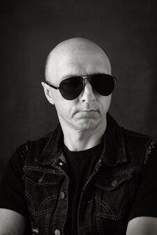 검은 t셔츠 데님 조끼와 어두운 안경에 형태가 이루어지지 않은 대머리 중년 남자