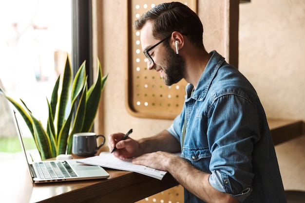 Unshaven brunette man wearing glasses writing and using earpod with laptop while working in cafe indoors