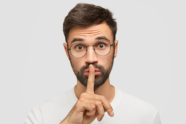 Unshaven caucasian male makes silence gesture, asks to be quiet as someone sleeps, wears spectacles, has trendy haircut, isolated over white wall. people, conspiracy and secrecy concept
