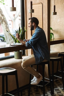 Unshaven caucasian man wearing denim shirt using earpod and cellphone with laptop while working in cafe indoors