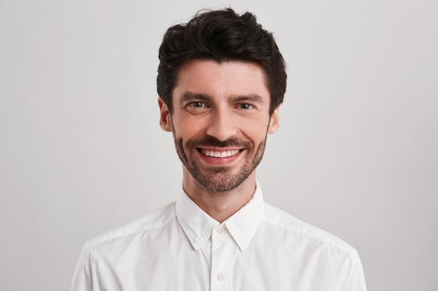 無精ひげを生やした自信を持って笑顔の男性、カジュアルな白いシャツを着て、彼の仕事に満足しています。