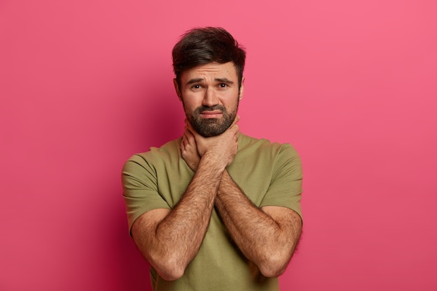 L'uomo dispiaciuto con la barba lunga tiene le mani sul collo, soffre di soffocamento